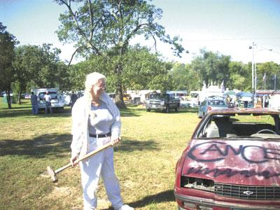 Daily Journal reporter, Paula Barr, takes a swing at a car to raise money for Relay for Life of St. Francois County Saturday at the Leadwood Fall Festival. - Jessica Crepps | Daily Journal